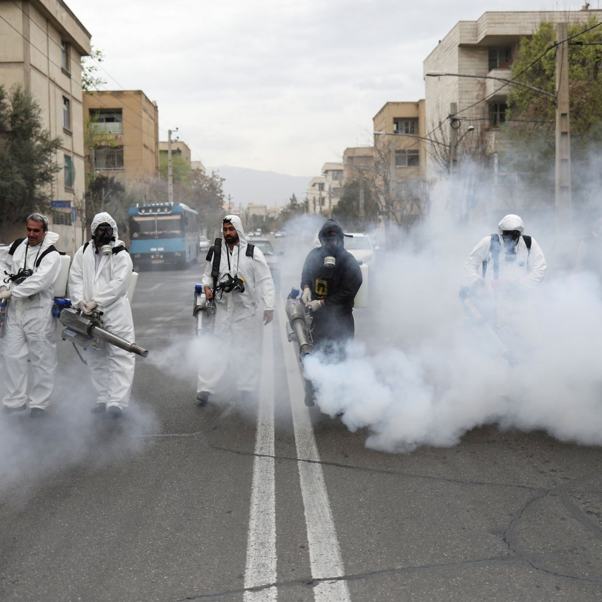 Firefighters wear protective face masks, amid fear of coronavirus disease (COVID-19), as they disinfect the streets ahead of the Iranian New Year holiday, in Tehran, Iran March 18, 2020.