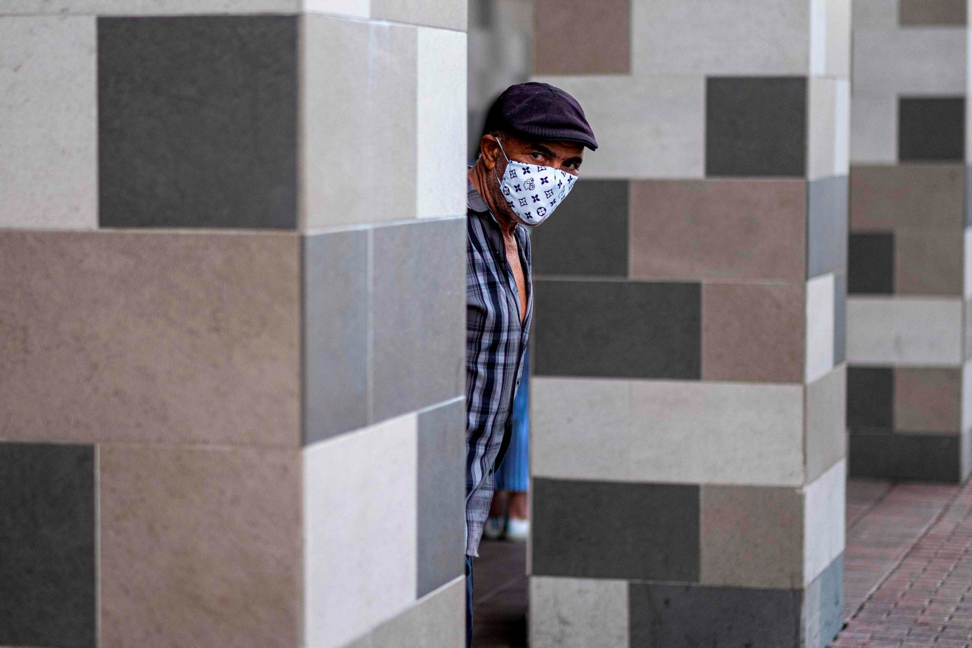 A man wears a face masks to protect against the coronavirus as he queues at a supermarket in San Juan, Puerto Rico on April 7, 2020.