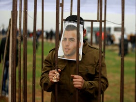 A Palestinian man playing the role of Israeli soldier Oron Shaul stands in a mock jail during a rally in solidarity with Palestinian prisoners held in Israeli jails, in the northern Gaza Strip December 29, 2017.