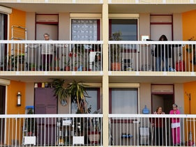People attend a fitness lesson from their balconies at a retirement home in Bordeaux, on March 31, 2020, as the country is under lockdown to stop the spread of the coronavirus.