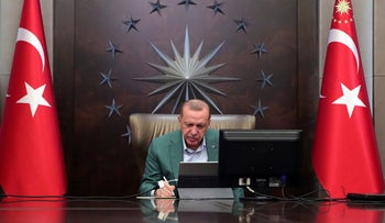 President Recep Tayyip Erdogan participates in a teleconference with his ministers amid the coronavirus outbreak, in Ankara, Turkey, Monday, March 23, 2020.