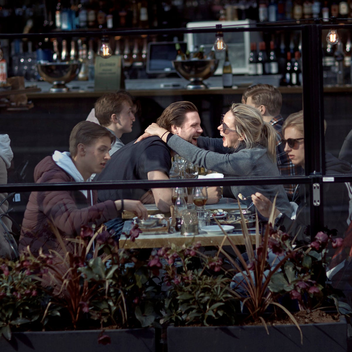 A couple hug and laugh as they have lunch in a restaurant in Stockholm, Sweden, Saturday, April 4, 2020.