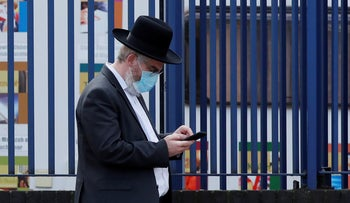 An Orthodox Jewish man wearing a protective face mask looks at his cellphone as the spread of the coronavirus disease continues, London, April 6, 2020.