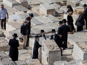 Ultra-Orthodox Jews attend a funeral in Jerusalem's Mount of Olives cemetery, March 25, 2020.