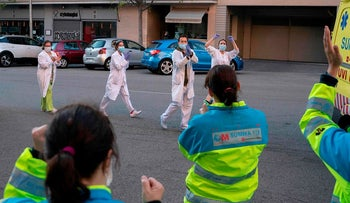 In this handout picture made available on April 9, 2020 by the Comunidad de Madrid (Madrid regional government) members of the Comunidad de Madrid's Biological Risk Medical Emergency Service and healthcare workers applaud each other in Madrid