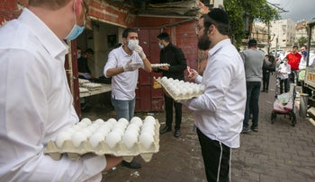 A man buys eggs in Bnei Brak during the closure of the city, April 10, 2020