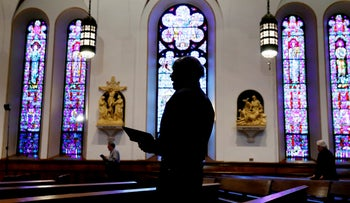 A church member prays during a Good Friday service at St. Ambrose Cathedral, Iowa, April 10, 2020