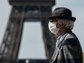 A man wearing a face mask walks near the Eiffel tower in Paris on the 22nd day of a lockdown in France aimed at curbing the spread of the COVID-19 pandemic, caused by the novel coronavirus. (Photo by )