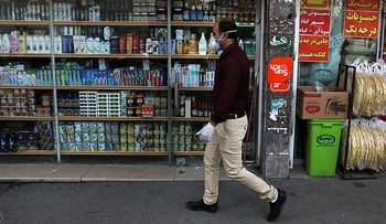 A man wearing a face mask and gloves to protect against the new coronavirus walks past a grocery in northern Tehran, Iran, Saturday, April 4, 2020.