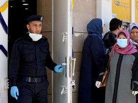 A Palestinian policeman stands guard as a woman, wearing a mask as a precaution against the coronavirus, waits with other people outside a bank to withdraw cash, Gaza City, March 29, 2020.