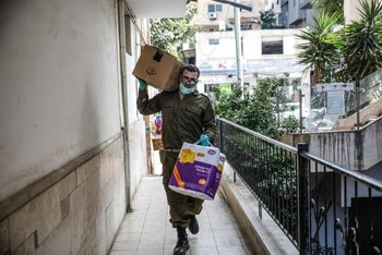 Israeli soldier bringing food aid to families in need Bnei Brak under coronavirus lockdown, April 7, 2020.