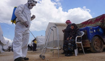 A member of the Syrian civil defense, also known as the White Helmets, sprays disinfectant on a walker outside a tent, near the town of Maaret Misrin in Syria's northwestern Idlib province, April 9, 2020.