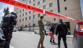 Israeli soldiers and policemen put up a road barrier in Jerusalem's Bayit VeGan neighborhood, as part of the efforts to combat the spread of the coronavirus in the city.
