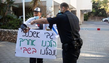 A protesters outside the home of Gabi Ashkenazi in Kfar Saba and a police officer, April 13, 2020.