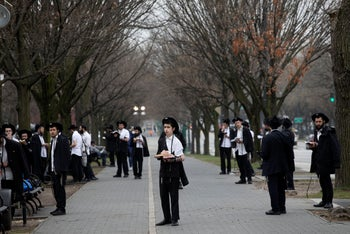 """Orthodox men practice """"social distancing"""" as they pray outside the Chabad Lubavitch World Headquarters, in the Brooklyn borough of New York, March 20, 2020."""