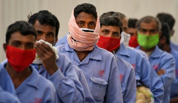 Foreign workers wearing scarves to protect their faces stand in line to board a bus transporting them to their workplace, in Dubai, April 2, 2020.