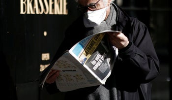 A man wearing a protective mask reads a newspaper.
