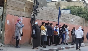 Women wait in line at a bus stop in Jisr al-Zarqa, April 2020. Little social distancing to prevent the spread of the coronavirus.