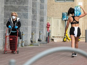 An Israeli woman wearing a protective mask as another woman carries a six-pack of mineral water, April 2020.