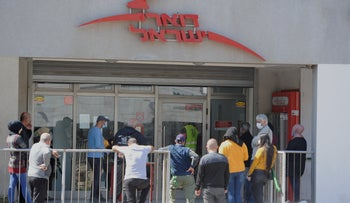 People stand in line at the post office in Israeli Arab city Umm al-Fahm, Aril 14, 2020