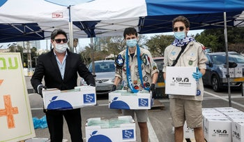 Social Services Minister Ofir Akunis, left, helping to distribute food to needy families in Tel Aviv.