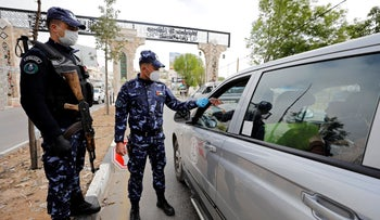 Palestinian police officers check the identity card of a vehicle's occupant during a home-confinement order to prevent the spread of the coronavirus, in Hebron, the West Bank, April 7, 2020.