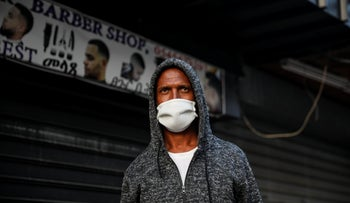 A man wearing a protective mask in front of a shuttered store in a normally busy street of South Tel Aviv, March 31, 2020.
