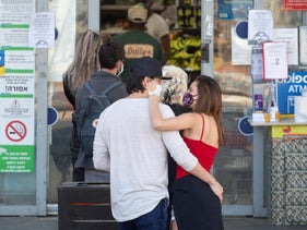 An Israeli couple queues to enter a store in Tel Aviv during the coronavirus pandemic, April 12, 2020.