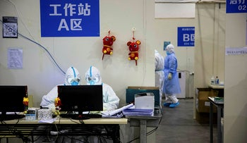 Medical staff members working at an exhibition center converted into a hospital in Wuhan in China's central Hubei province, February 17, 2020 .