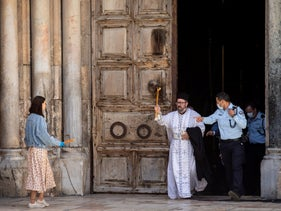 The sacred fire is taken out of the Church of the Holy Sepulcher in Jerusalem on Saturday, April 18, 2020.