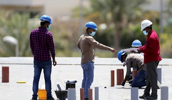 Workers wearing protective face masks work on a residential construction site, following the outbreak of coronavirus in Dubai, United Arab Emirates, April 14, 2020.