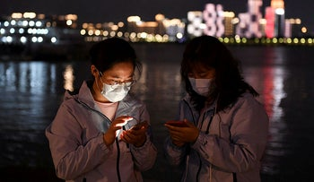 Medical workers from outside Wuhan check their mobile phones at a riverside park by the Yangtze River in Wuhan, March 26, 2020.