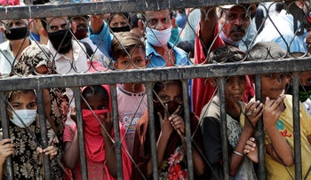 Men and children wait to receive free food distributed during lockdown due to the spread of the new coronavirus in Mumbai, India, Saturday, April 18, 2020.