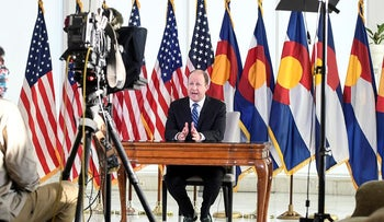 Colorado Gov. Jared Polis, right, delivers an address from the governor's mansion Monday, April 6, 2020, in Denver.