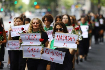 Women hold signs with the names of femicide victims at a protest marking International Women's Day in Buenos Aires, Argentina. March 8, 2020
