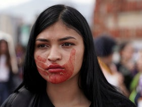 A woman, with a red hand marked on her face to denounce gender violence, takes part in a march to mark International Women's Day in Bogota, Colombia March 8, 2020