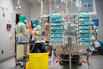 Nurses wearing protective clothing and face masks take care of a COVID-19 patient at the Karolinska hospital in Solna, near Stockholm, Sweden, on April 19, 2020