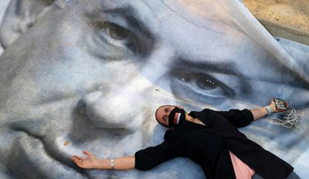 A woman lies atop a banner of Netanyahu at the 'Black Flag' protest against antidemocratic measures taken in the face of the coronavirus crisis, April 19, 2020.