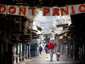 """A woman walks under a """"don't panic"""" sign at entrance of a market that was shut down in order to reduce the spread of the coronavirus, Tel Aviv, March 23, 2020"""