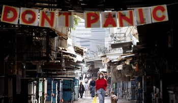 "A woman walks under a ""don't panic"" sign at entrance of a market that was shut down in order to reduce the spread of the coronavirus, Tel Aviv, March 23, 2020"