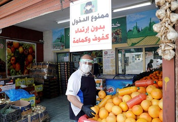 An Israeli Arab shop owner wears a mask and gloves in the  village of Deir el-Assad, on April 16, 2020.