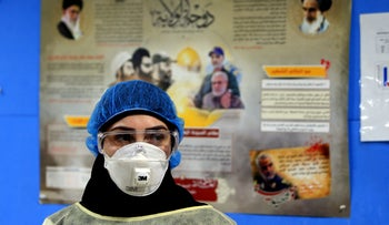 A nurse in protective clothing in front of a poster in praise of Iran and Hezbollah at a hospital in Beirut's southern suburb, March 31, 2020.