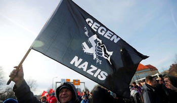 "A demonstrator holds a flag reading ""Against Nazis"" during a protest against a march of far right groups following the 75th anniversary of the WW2 bombings in Dresden, Germany, February 15, 2020."