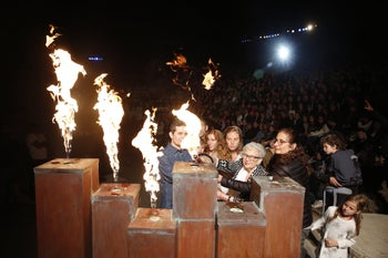A torch being lit at the Holocaust Remembrance Day ceremony at Yad Vashem. 2020 is the first year the event will not be live or with an audience.