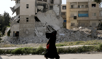A woman walks past damaged buildings with her child in the rebel-held Idlib city, Syria April 19, 2020.