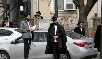 Men praying outside a synagogue stand apart because of the coronavirus pandemic, Brooklyn, New York, Tuesday, April 7, 2020.