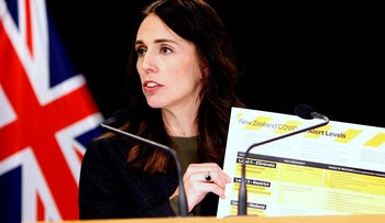 In this March 21, 2020, file photo, New Zealand Prime Minister Jacinda Ardern holds up a card showing a new alert system for COVID-19 in Wellington, New Zealand