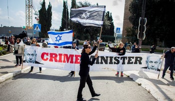 People wave Israeli flags during a'Black Flag'protest outside the Israeli parliament, Jerusalem, March 19, 2020