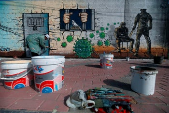 A Palestinian artist paints a mural in a show of support for Palestinian prisoners held in Israeli jails amid the COVID-19 pandemic. Gaza City, April 20, 2020