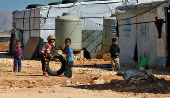 In this June 20, 2017 file photo, Syrian refugee children play outside their family tents at a Syrian refugee camp in the eastern city of Baalbek, Lebanon